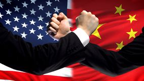 US vs China confrontation, countries disagreement, fists on flag background. Stock photo royalty free stock image