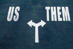 US vs THEM choice concept. Two direction arrows on asphalt Stock Photos