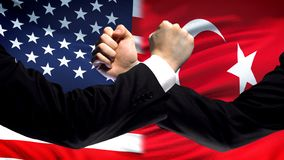 US vs Turkey confrontation, countries disagreement, fists on flag background. Stock photo stock image