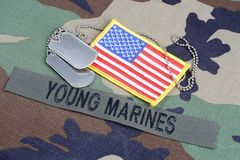 US YOUNG MARINES branch tape, flag patch and dog tags on woodland camouflage uniform. Background Stock Image