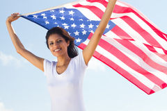 USA. Young happy beautiful woman holding a USA flag outdoors stock image