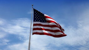 USA American Flag. Beautiful glowing footage of the American Flag flowing in the wind with a blue sky with white puffy clouds. HD 1080P stock video footage