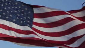 USA American Flag. Waving United states of America famous flag in front of blue sky. American flag is flying in the wind on a sunny day. Symbol of the Amenrican stock footage