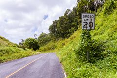 USA American style white Speed Limit 20 mph road sign with dirt rust rain stains overgrown in jungle. Pohnpei,Micronesia, Oceania. stock photos