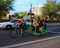 USA, Arizona/Tempe: Bike Taxi Driver and Passengers on St. Patricks Day. This bike taxi driver shows a Hispanic family Downtown Tempe on Saint Patricks Day Royalty Free Stock Images
