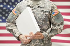 USA Army soldier holding big white box with two hands. U.A. Army soldier holding big white box with two hands Royalty Free Stock Images