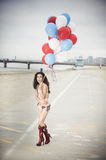 USA Bikini. Beautiful model wearing the United States flag bikini on skates holding USA color ballons at the beach sidewalk Royalty Free Stock Photography