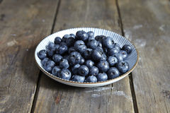 USA. Blueberries in a white plate on wooden background Stock Image