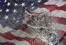 USA Border fence barb razor wire with American Flag Immigration Stock Images