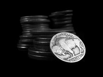 USA Buffalo Nickel. Close up view of a United States Buffalo Nickel with stacks of coins behind it on a black background Royalty Free Stock Images