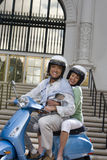 USA, California, San Diego, Balboa Park, senior couple riding on blue motor scooter near building steps, smiling, side view, portr Stock Images