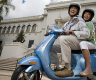 USA, California, San Diego, Balboa Park, senior couple riding on blue motor scooter, smiling, side view, portrait, low angle view Stock Image