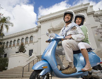 USA, California, San Diego, Balboa Park, senior couple riding on blue motor scooter, smiling, side view, portrait, low angle view Stock Photos