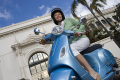 USA, California, San Diego, Balboa Park, senior woman riding on blue motor scooter, smiling, side view, low angle view (tilt) Stock Photography