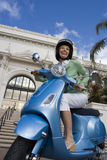 USA, California, San Diego, Balboa Park, senior woman riding on blue motor scooter, smiling, side view, low angle view (tilt) Stock Image