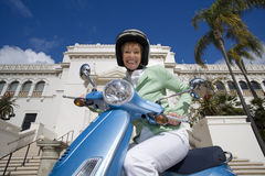 USA, California, San Diego, Balboa Park, senior woman riding on blue motor scooter, smiling, side view, portrait, low angle view Stock Photo