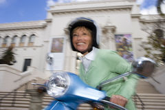 USA, California, San Diego, Balboa Park, senior woman riding on motor scooter, smiling, side view, low angle view (blurred motion) Stock Photos
