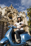 USA, California, San Diego, Balboa Park, woman riding on blue motor scooter, smiling, side view, low angle view Stock Photo