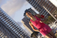 USA, California, San Diego, woman wearing pink sports vest and shorts, jogging, listening to MP3 player strapped to arm, smiling,  Stock Photography