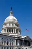 USA Capital Dome. With the flag waving against a blue sky background Royalty Free Stock Photo