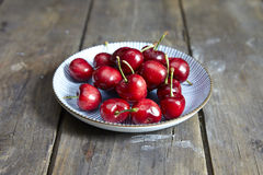 USA. Cherries in a white plate on wooden background Royalty Free Stock Photography