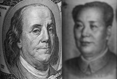 USA and China Currencies. Macro portraits of Benjamin Franklin and Mao Tse-Tung in the US and China currencies respectively. Shallow depth of field. Benjamin Stock Photo