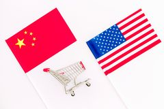 USA and China trade war. American and chinese flags near shopping chart on white background top view.  stock photos