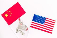 USA and China trade war. American and chinese flags near shopping chart on white background top view space for text. USA and China trade war. American and royalty free stock photo