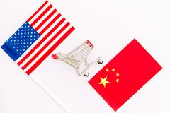 USA and China trade war. American and chinese flags near shopping chart on white background top view space for text. USA and China trade war. American and stock image