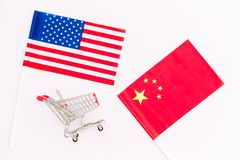 USA and China trade war. American and chinese flags near shopping chart on white background top view.  royalty free stock images