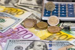 Usa coin, euro cent, one pound lying on dollar and euro bills  calculator. Usa coin, euro cent  one pound lying on dollar and euro bills, calculator, pen Royalty Free Stock Images
