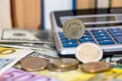 Usa coin, euro cent, one pound lying on dollar and euro bills. Calculator, pen Royalty Free Stock Photo