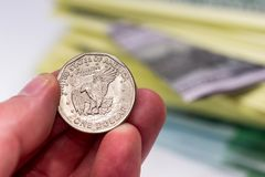 Usa coin in hand above dollar. Close up Stock Photo