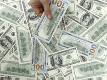 USA 100 dollar räkningar med 1 hand Arkivbild