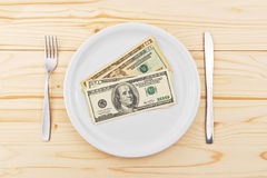 USA dollars served on plate as dinner. With fork and knife on sides. Eating money is conceptual metaphor for greed Royalty Free Stock Image