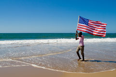 USA flag. Young african american man running with USA flag on beach Stock Photography