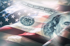 USA flag and American dollars. American flag blowing in the  wind and 100 dollars banknotes in the background.  Stock Image