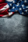 USA flag. American flag. American flag freely lying on concrete background. Close-up Studio shot. Toned Photo Stock Image