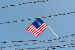 USA flag on barbed wire fence with sky background. American flag on old barbed wire fence with blue sky background. Borders protection,social issues on refugees stock images
