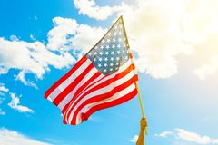 USA flag with clouds on background and flare visible Stock Photo
