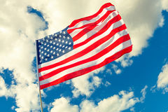 USA flag with cumulus clouds on background. Filtered image: cross processed vintage effect. Royalty Free Stock Photos