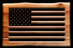 The USA flag cut in a wooden board, plate isolated on black. Royalty Free Stock Images