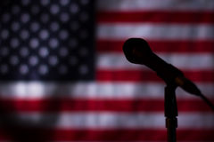 USA flag in the darkness. Banner and microphone in darkness. Midnight at radio station. Broadcast is over stock photo