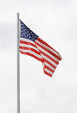 USA flag on flagpole. Against cloudy sky Stock Photo