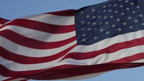 Close up of American flag waving. USA flag flaping in wind. Elegant Nylon American Flag Waving in the Wind. Close-up of an American flag flying in the wind stock footage