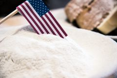 USA flag in flour, slices of bread on the background, dark tone. Financial crisis, poverty, great depression concept. stock image