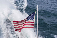 USA Flag. In front of a wake made by a boat Stock Images