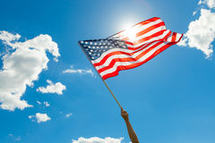 USA flag in hand with beautiful white clouds and blue sky on background Royalty Free Stock Image