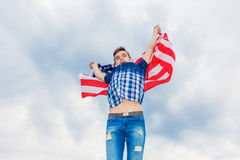 USA flag is held by a running guy in the background of a summer sky Royalty Free Stock Photo