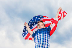 USA flag is held by a running guy in the background of a summer sky Stock Photography